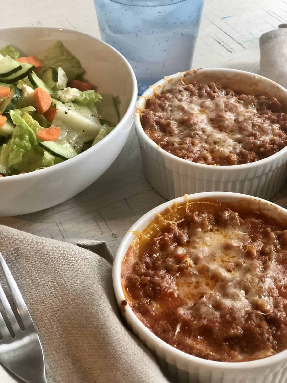 two individual butternut squash lasagnas in white ramickens with a tan napkin fork and a bowl of salad a tan napkin and a glass of lemonade