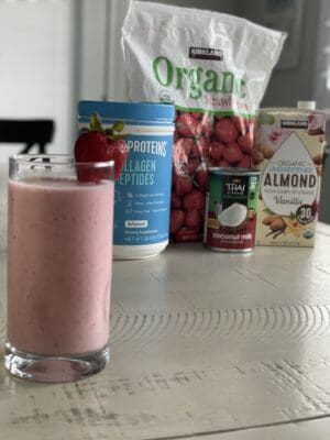 low sugar strawberry smoothie in a glass and garnished with a strawberry and collagen protein frozen strawberries almond milk and coconut cream in the back round