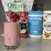a low sugar strawberry smoothie in a glass with a strawberry for garnish in front of smoothie ingredients including frozen strawberries canned coconut cream collagen peptides and kirkland signature almond milk