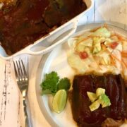 plate of enchilada layers with diced avocado, green salad, and baking dish with enchiladas