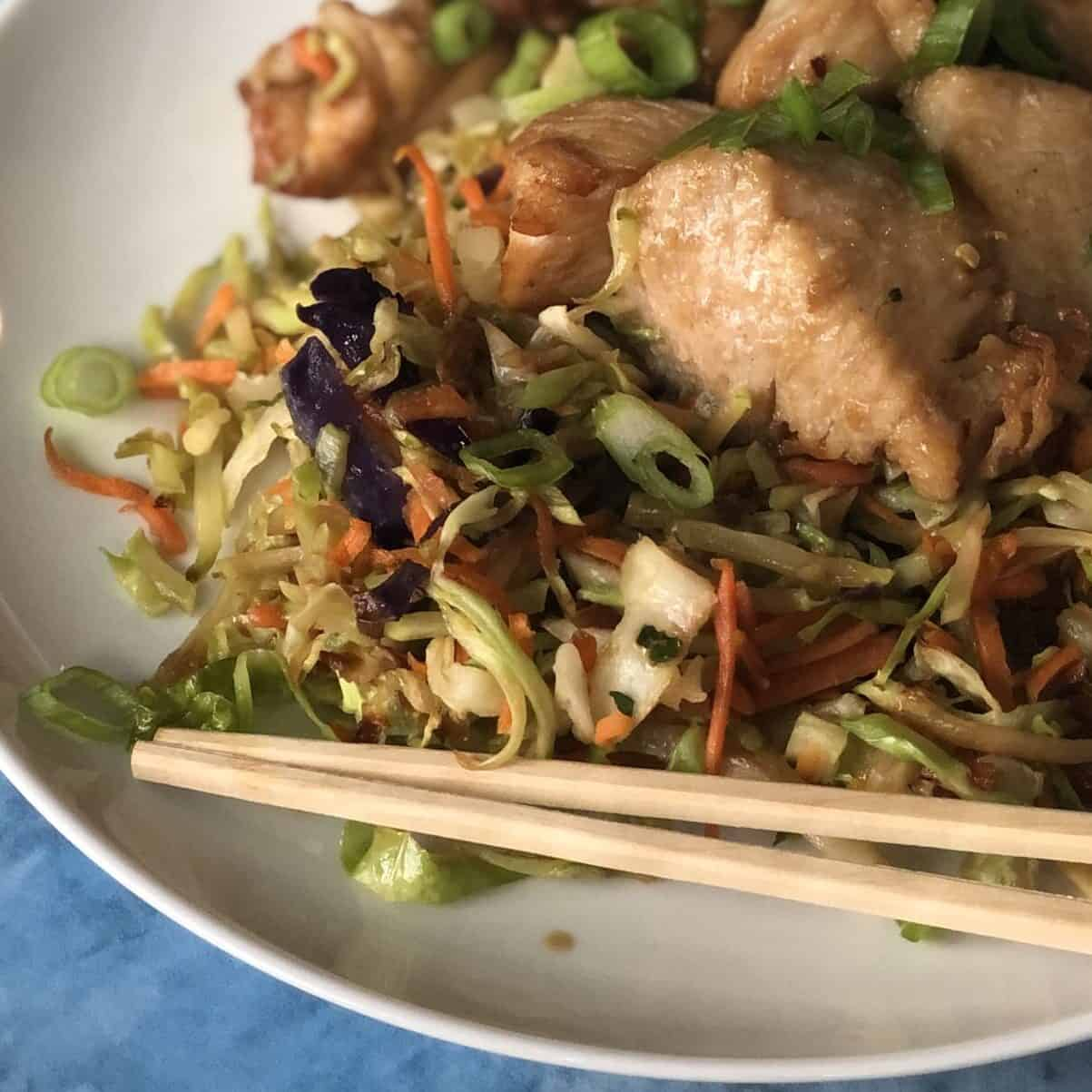 plate of stir fried veggies and chicken with chopsticks