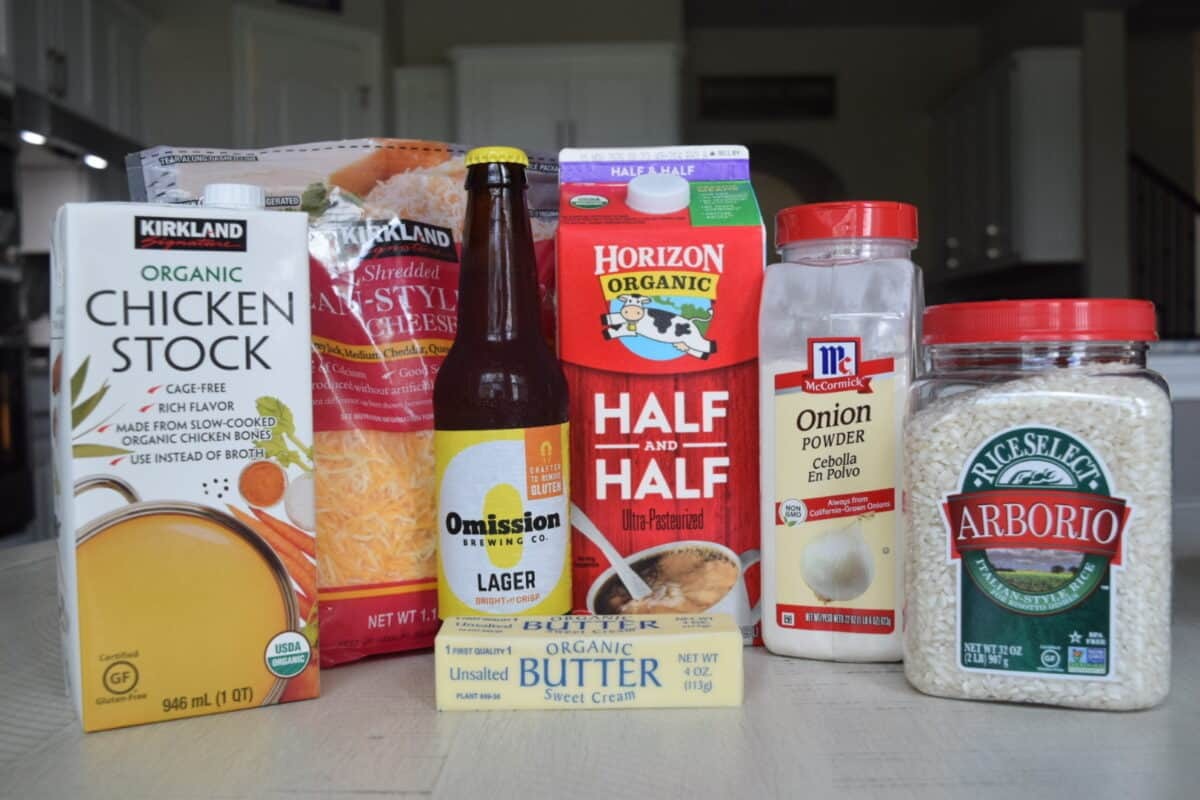 Ingredients from left to right: Kirkland Signature Chicken Stock, Kirkland Signature Shredded Mexican Style Cheese Blend, Omission Lager, Horizon Half and Half, Kirkland Signature Butter, McCormick Onion Powder, and Arborio Rice.