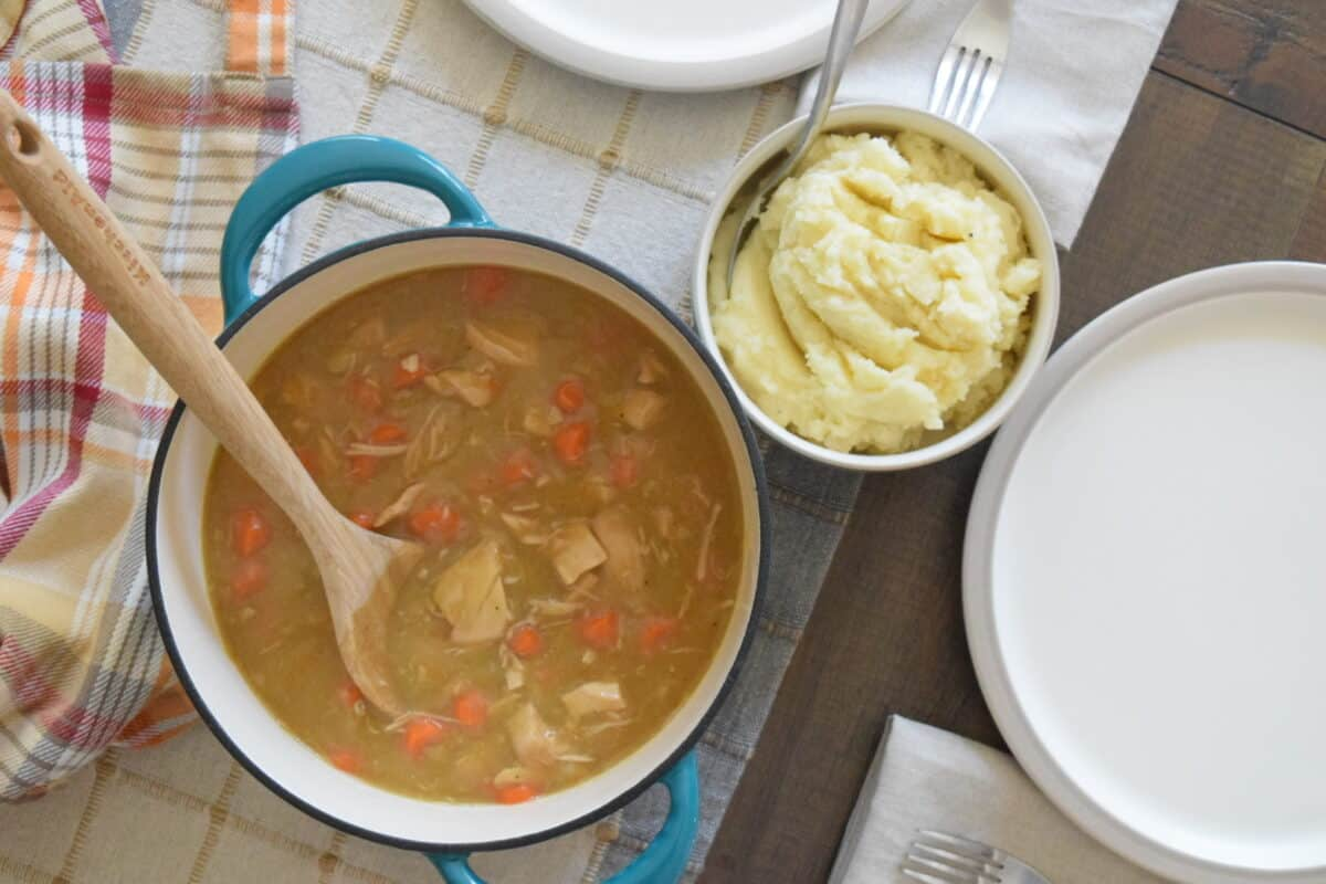 dining table with a teal pot of rotisserie chicken stew a bowl of mashed potatoes 2 plates forks napkins and an apron