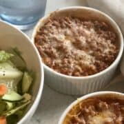 an individual butternut squash lasagna topped with melted cheese a bowl of green salad and glass of water