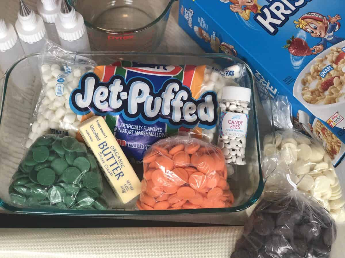 box of rice krispie cereal bag of marshmallows 4 plastic piping bottles a stick of butter bottle of candy eye sprinkles and orange green, white and brown chocolate candy melts