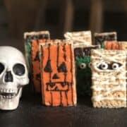 plastic skull halloween decoration and rice krispie treats decorated like a mummy frankenstein and jack-o-lantern