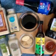 a bottle of soy sauce honey sesame oil next to spice containers of garlic onion ginger powder white pepper and an orange spatula on a wood cutting board with blue background
