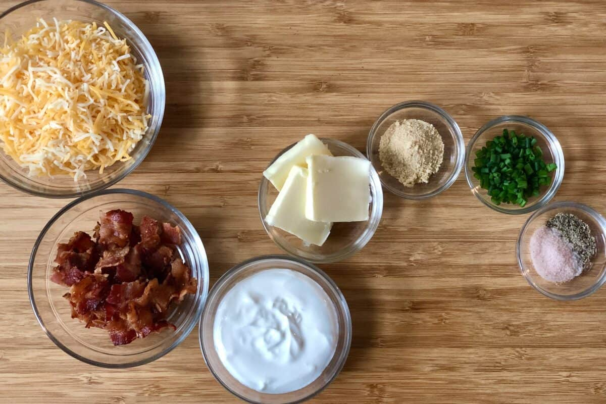 wood cutting board with glass bowls of ingredients including shredded cheese bacon sour cream butter onion powder chives salt and pepper
