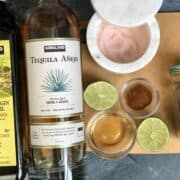 a bottle of kirkland signature tequila and olive oil with a lime cut in half jar of salt and chili powder