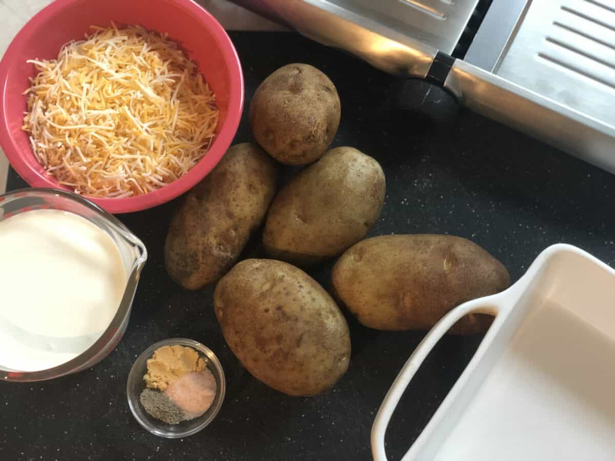 5 russet potatoes on a black cutting board next to a measuring cup of cream red bowl of shredded cheese a small bowl of spices with a partial view of a mandolin and white baking dish