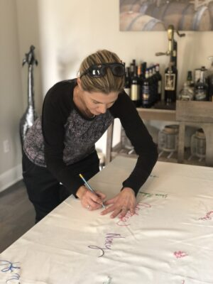 A woman signing a tablecloth that is spread out on a dining room table