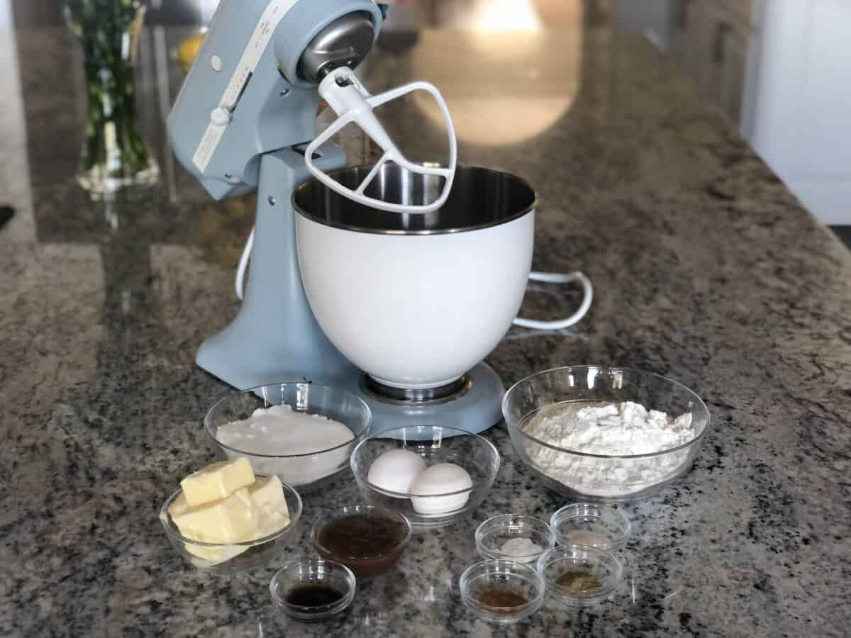 a light stand mixer with paddle attachment and white bowl behind small glass mixing bowls with apple butter and cardamom cookie ingredients