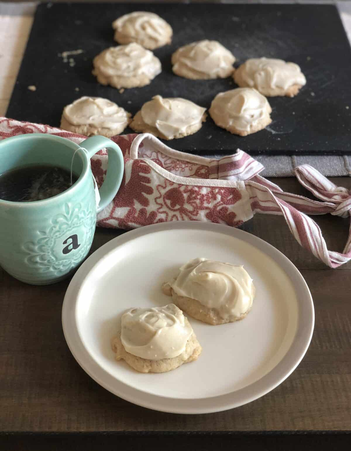 a tan colored plate with two apple and cardamom cookies next to a teal coffee mug on a table with a pink apron and more cookies on a black cutting board in the background all set on a wood dining table