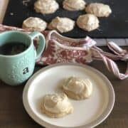 small plate with two frosted apple butter and cardamom cookies with a pink apron and more frosted cookies on a black cutting board