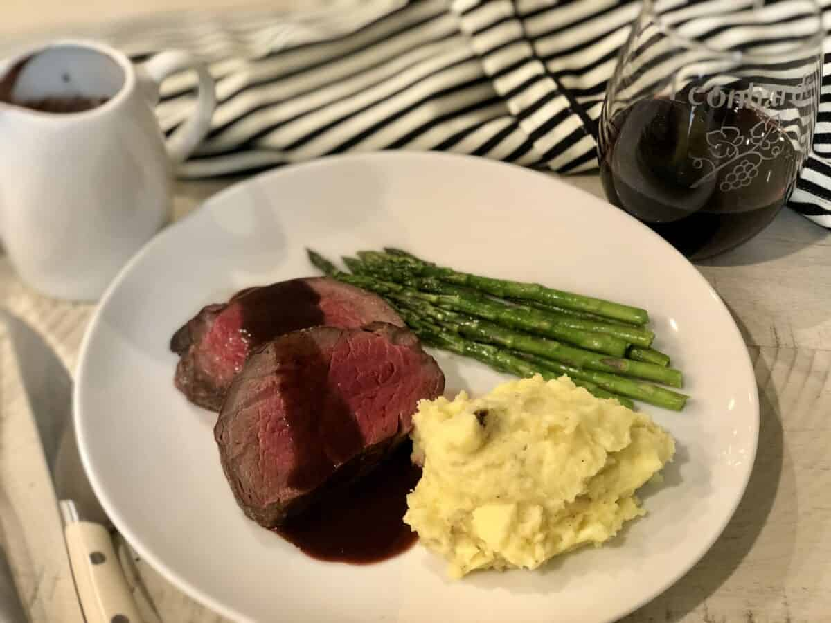 a white plate with medium cooked beef tenderloin served with red wine sauce mashed potatoes and asparagus a glass of red wine and a serving dish of sauce with a black and white apron in the backround