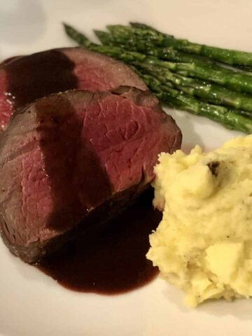 two slices of beef tenderloin cooked medium with red wine sauce served on a plate with mashed potatoes and asparagus