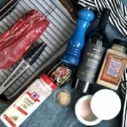 ingredients for a beeftenderoin and red wine sauce including a beef tenderloin on a sheet pan with wire rack and tongs onion powder better than bouillon a blue pepper grinder garlic powder salt jar and bottle of kirkland signature red blend