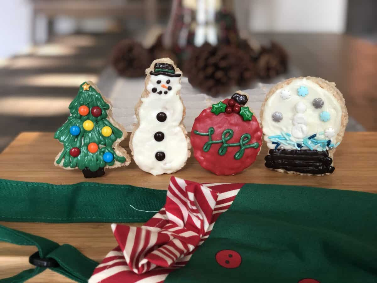 4 decorated christmas rice krispie treats in the shape of a christmas tree snowman ornament and snow globe are standing up on a brown cutting board with a green and red apron showing and pine cone in the background