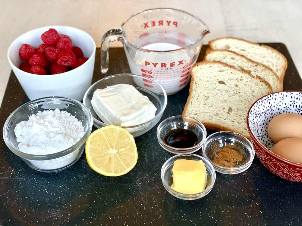 a white bowl of raspberries a glass bowl of powdered sugar half a lemon half a block of cream cheese half a cup pf half and half 4 slices of bread a small bowl of vanilla extract a small bowl of butter a small bowl of spices and 2 brown eggs in a red bowl