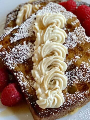 2 white plates with cooked french toast dressed up with cheesecake filling powdered sugar fresh raspberries and maple syrup