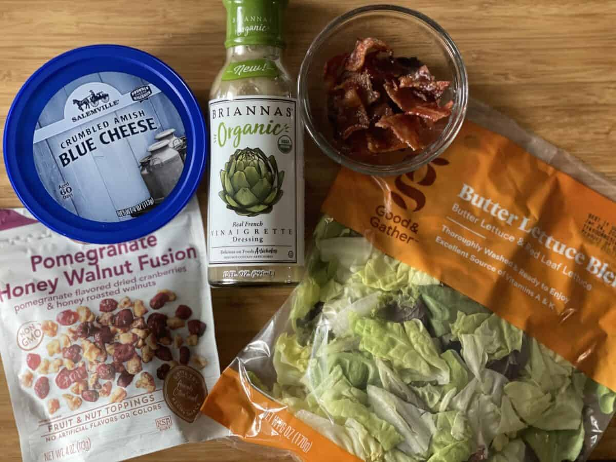 packaged ingredients for the salad including dried cranberry and walnut topping crumbled blue cheese french vinaigrette crumbled bacon and a bag of butter lettuce