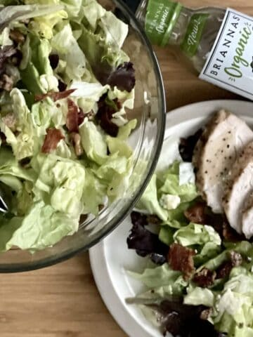 A light wood cutting board with a glass bowl filled with cranberry walnut and blue cheese salad next to a plate with salad and grilled chicken