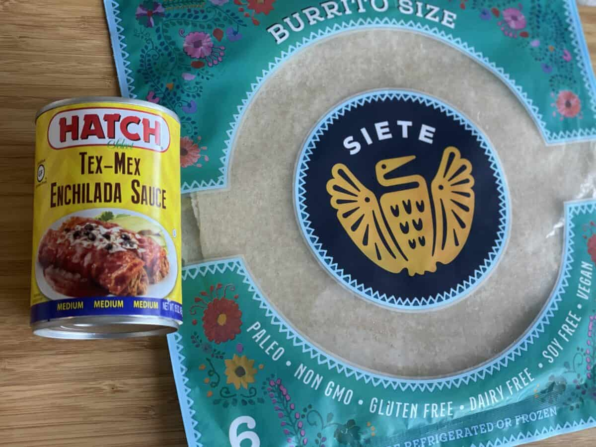 a can of hatch tex mex enchilada sauce and site brand burrito size tortillas on a wood cutting board