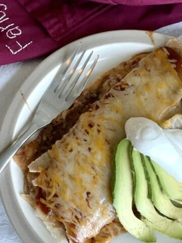 a plate with an enchirito smothered in cheese served with avocado sour cream a fork and an apron next to it