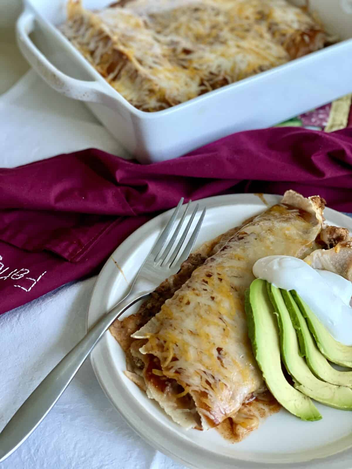 cooked beef and bean enchiritos on a white plate with sliced avocado and sour cream with the baking dish and more enchiritos behind the plate