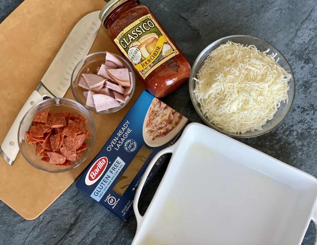 a light brown cutting board and knife with bowls of prepared pepperoni canadian bacon jarred pasta sauce shredded mozzerella cheese no boil lasagna sheets and a white baking dish