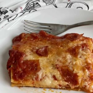 large slice of pizzagna on a white plate with a baking dish of more paizzanga in the back round and a black and white tea towel in between
