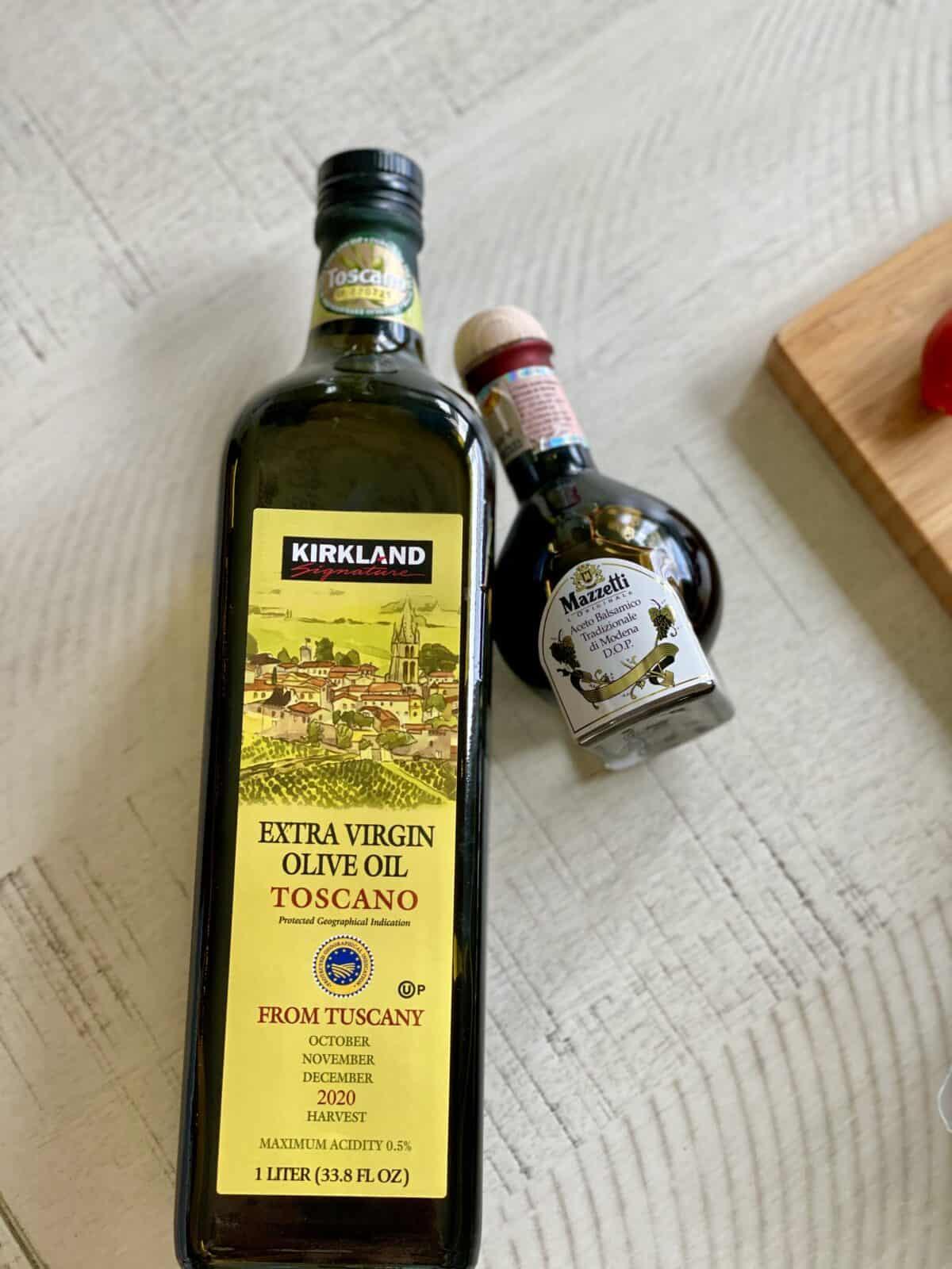 a bottle of kirkland signature extra virgin olive oil and a bottle of mazetti balsamic vinegar
