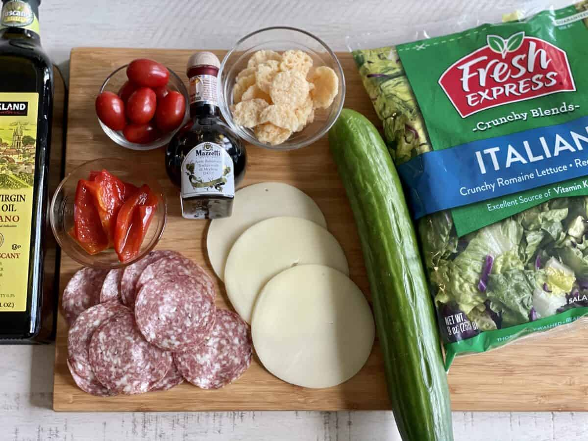 from left to right Kirkland signature extra  virgin olive oil a bowl of grape tomatoes roasted red bell peppers dry italian salami provolone cheese balsamic vinegar parmesan crisp salad toppings a large english cucumber and a bag of italian salad greens on a large brown cutting board