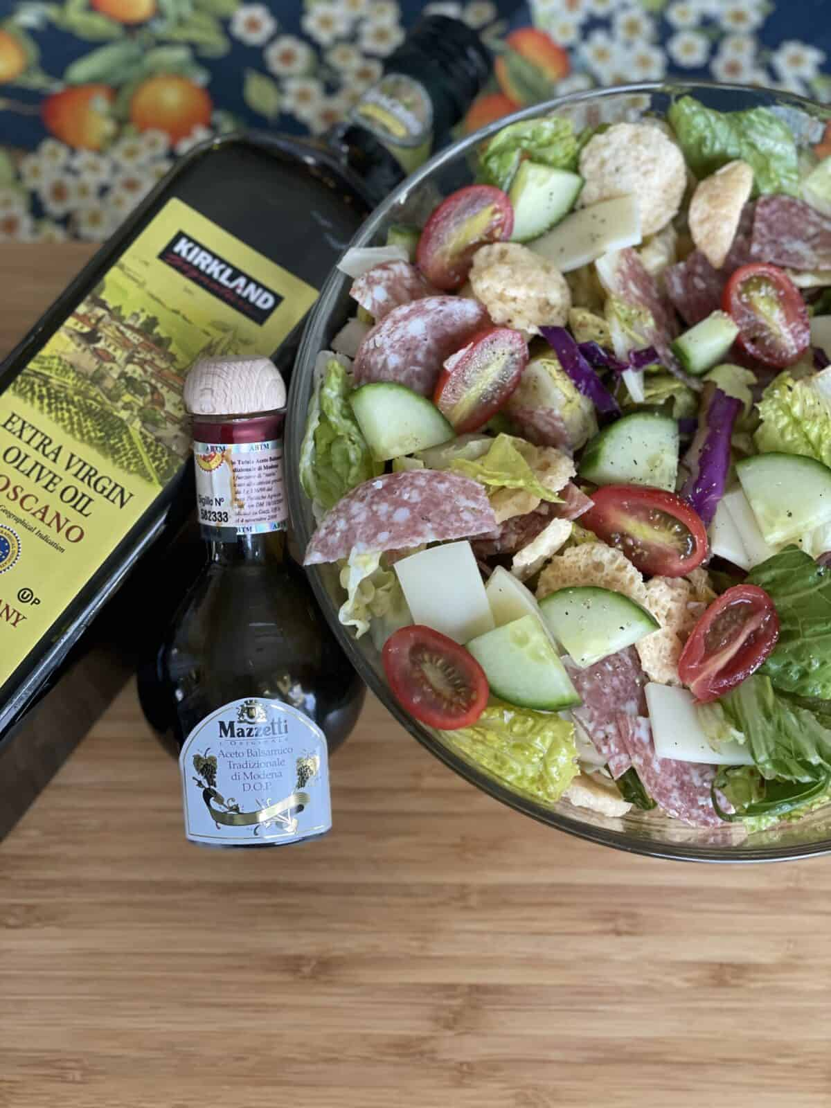a big glass bowl of Italian chopped salad on a light brown cutting board next to a bottle of kirkland signature olive oil and mazzeti balsamic vinegar