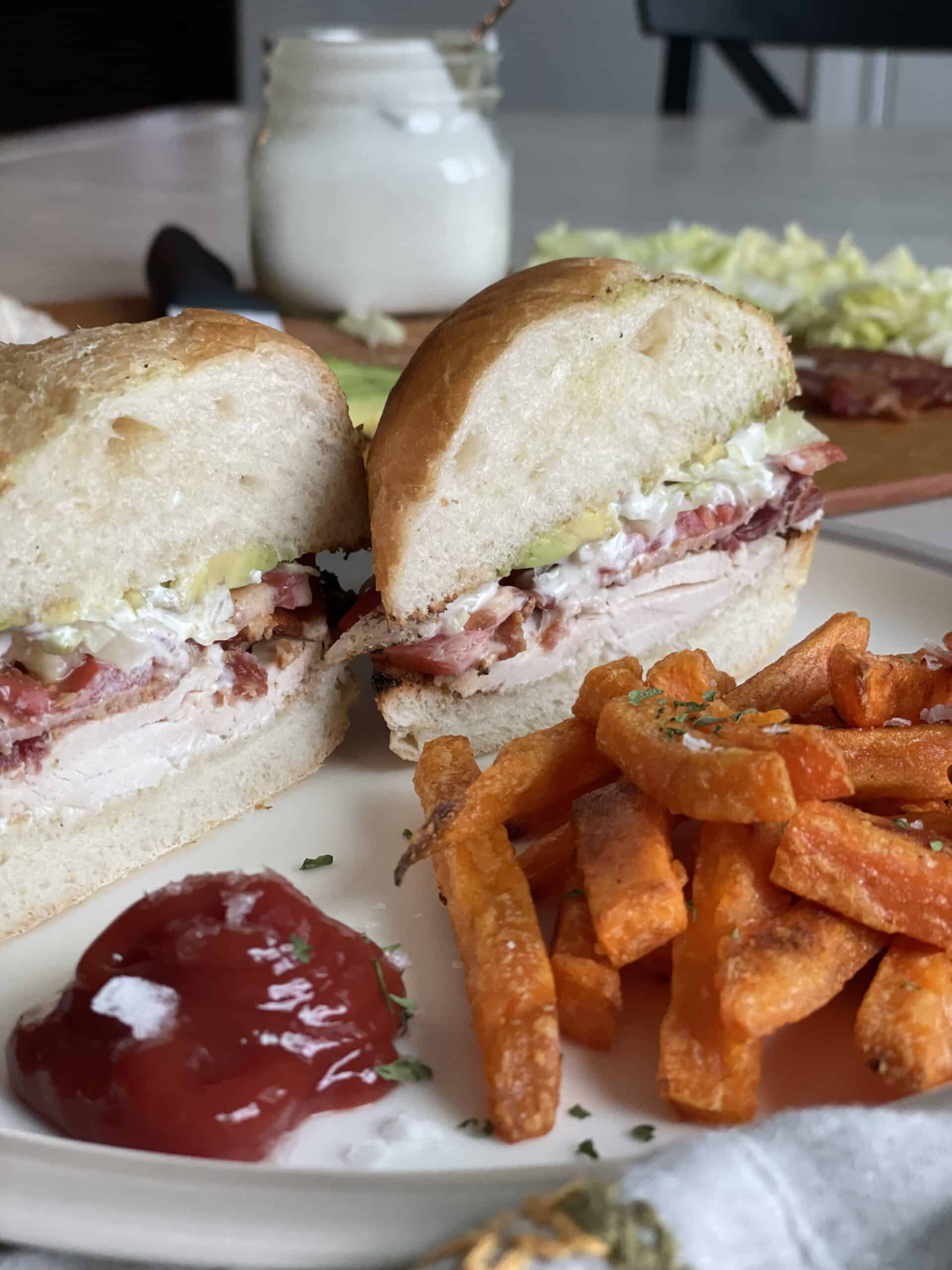 a white plate with a chicken cob sandwich cut on a diagonal with sweet potato fries ketchup and a jar of blue cheesing in the background